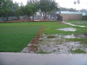 heavy rain falling on artificial turf and real grass