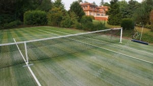 artificial sand filled turf tennis court installation with house in background