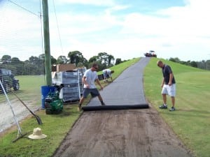 men rolling out geosynthetic fabric for tee line install