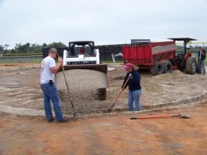 a front end loader places gravel in drainage system trench