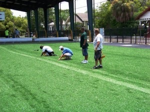 installers nailing down artificial turf at seam