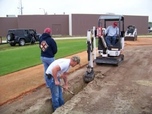 artificial turf field installers dig a trench for base panel system drainage