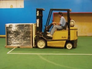 man uses forklift to lift a stack of ultrabasesystems panels for indoor soccer field