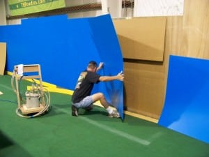 man removing old dasher boards during indoor soccer field installation