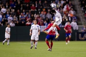 soccer player jumps into the air to head but soccer ball