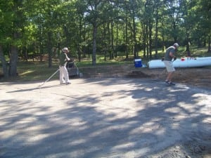 installers spreading and flattening dirt area for putting green installation